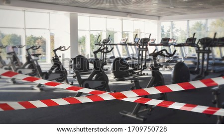 Quarantine Zone Warning Tape, Do Not Cross. Red and white hazard safety stripes across empty closed gym club center #1709750728