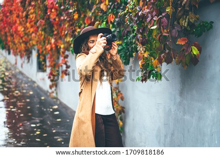 Curly girl in hat takes pictures on a camera on the background of an autumn vineyard.