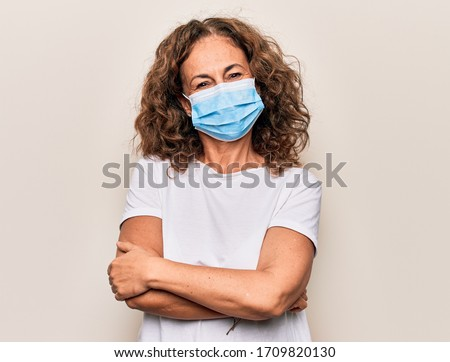 Middle age woman wearing coronavirus protection mask for covid-19 epidemic virus happy face smiling with crossed arms looking at the camera. Positive person. #1709820130
