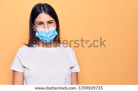 Young woman wearing protection mask for coronavirus disease over yellow background with a happy and cool smile on face. Lucky person. #1709839735