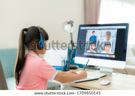 Asian girl student video conference e-learning with teacher and classmates on computer in living room at home. Homeschooling and distance learning ,online ,education and internet. #1709850145