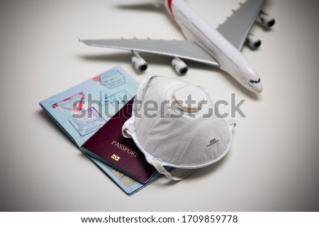 Travelling during corona virus epidemic. Passport and protective face mask respirator. Coronavirus and travel concept. Travelling with face mask. Corona virus prevention. Flights cancelled. Stay Home. #1709859778