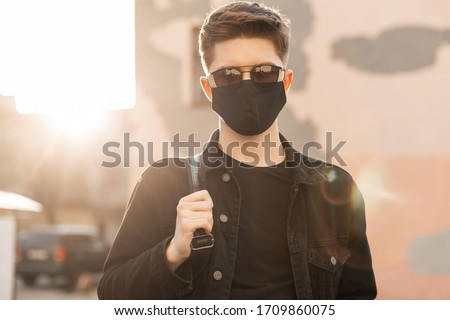 Young trendy man in youth casual clothes in sunglasses in protective black mask walks on city at sunset. Fashionable teenager guy enjoys in bright sunlight. Spring. Modern Fashion 2020. #1709860075