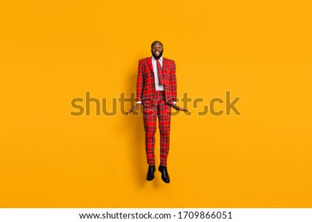 Full length photo of crazy funny dark skin guy jump high up spend best free time leisure wear checkered red costume blazer pants shoes isolated bright yellow color background Royalty-Free Stock Photo #1709866051