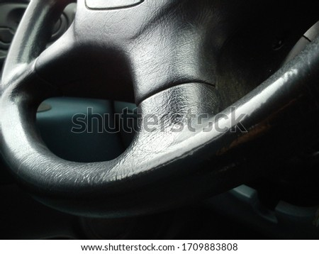 Vehicle interior. Dark steering wheel. The interior of the car cab. Dark upholstery. Vehicle keys in the contact slot. Round steering wheel. #1709883808