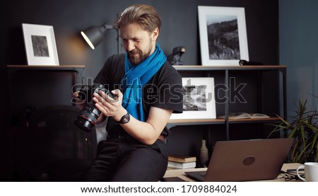 Half-length shot of photographer reviewing taken pics in DSLR camera sitting on table in studio