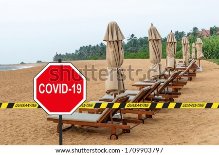 ''COVID-19'' road sign and a quarantine warning tape against loungers and folded beach umbrellas in a desolate tropical beach Royalty-Free Stock Photo #1709903797