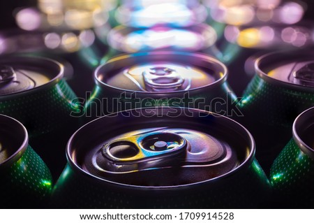 A close-up of green beer cans lit with colorful light. The cans are close together. The cans are printed with dots. In the background, the cans are out of focus with bokeh.