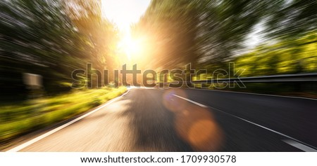 Empty long mountain road to the horizon on a sunny summer day at bright sunset with motion blur, Backplate or Backdrop background.