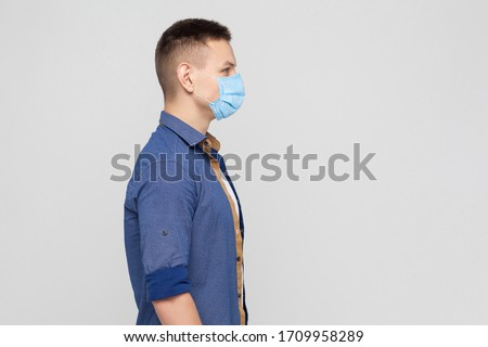 Side view, protection against contagious disease, coronavirus. Man wearing hygienic mask to prevent infection, airborne respiratory illness, Covid-2019. indoor studio shot isolated on gray background Royalty-Free Stock Photo #1709958289