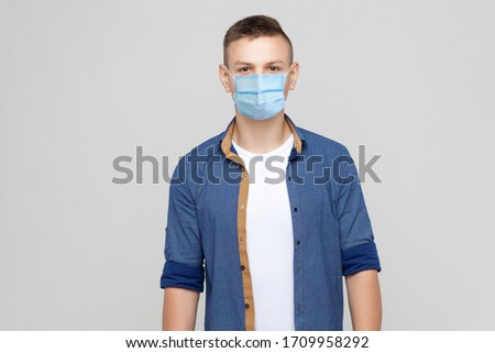 Protection against contagious disease, coronavirus. Man wearing hygienic mask to prevent infection, airborne respiratory illness such as flu, Covid-2019. indoor studio shot isolated on gray background #1709958292
