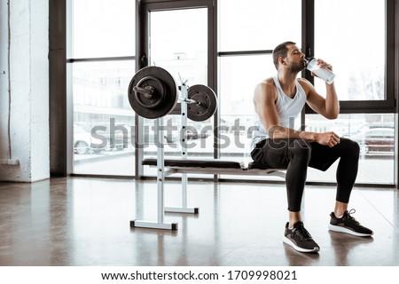 handsome sportsman drinking protein milkshake near barbell in gym #1709998021