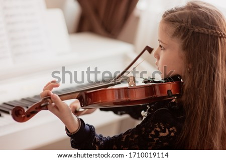 Home lesson for a girl playing the violin. The idea of activities for children during quarantine. Music concept Royalty-Free Stock Photo #1710019114