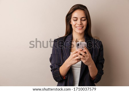 Photo of cheerful businesswoman in formal suit smiling and using cellphone isolated over white background #1710037579