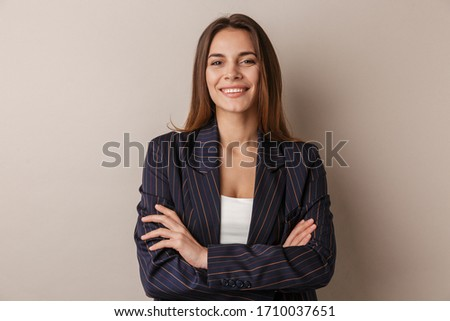 Photo of joyful businesswoman in formal suit smiling at camera with arms crossed isolated over white background #1710037651