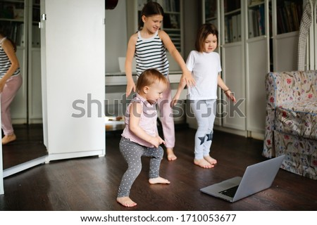 Three children are engaged in dancing, aerobics in video chat online with laptop, siblings dancing in front of laptop camera. kids remote sports and dancing, children's sports sections online. #1710053677