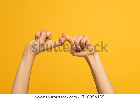Cropped view of woman showing friends word from sign language isolated on yellow #1710056155