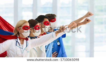 International doctor and nurse team wearing surgical face mask in superhero cape. Medical staff during coronavirus outbreak. Super hero power for clinic and hospital personal. Covid-19 pandemic. Royalty-Free Stock Photo #1710065098