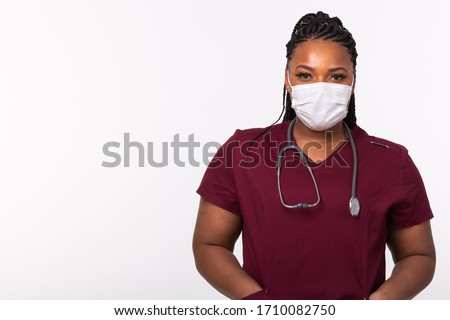 African american doctor in a medical mask over white background with copy space. Medicine, healthcare and people concept. Royalty-Free Stock Photo #1710082750