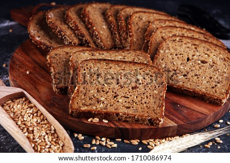 Sliced rye bread on cutting board. Whole grain rye bread with seeds on rustic background #1710086974