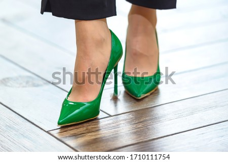 new green shoes on the girl's legs close-up. Shoes - shoes covering the leg no higher than the ankle. Heel stiletto heel on new designer shoes. green elements of female accessories. Royalty-Free Stock Photo #1710111754