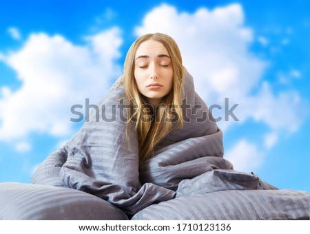 creative image: Girl woman in bed after sleep at the sky background isolated, sleep female, stay at home concept, coronavirus quarantine, wake up in the morning