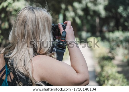 Blonde woman uses a DSLR camera to take photos in nature