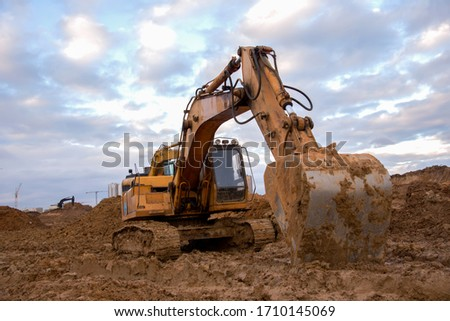 Excavator working at construction site. Backhoe digs ground for the foundation and for paving out sewer line. Construction machinery for excavating, loading, lifting and hauling of cargo on job sites #1710145069