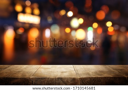 background Image of wooden table in front of abstract blurred restaurant lights #1710145681
