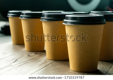 A line of disposable coffee cups on a wooden table. Brown paper cup with black lid  #1710159787