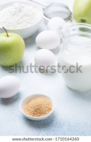 Milk, flour, eggs and green apples on a white background. Ingredients for apple charlotte. Recipe. #1710164260