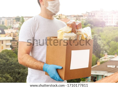Coronavirus Donation box. Delivery food. Volunteer. Food help. A man in a mask and medical gloves holds a box of food on the street. Coronavirus volunteer. Quarantine  #1710177811