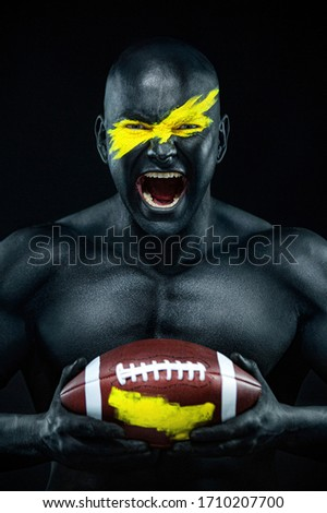 American football fan with ball on black background. Fitness and sport motivation. Strong fit and athletic guy in body paint like a super hero. Royalty-Free Stock Photo #1710207700