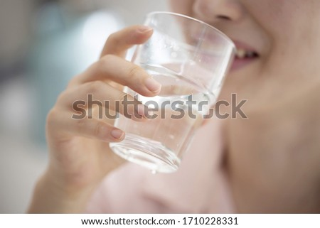 Close up of woman drinking glass of water #1710228331
