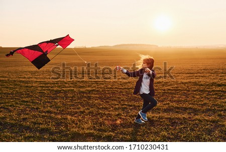 Happy little girl running with kite in hands on the beautiful field at sunrishe time. #1710230431