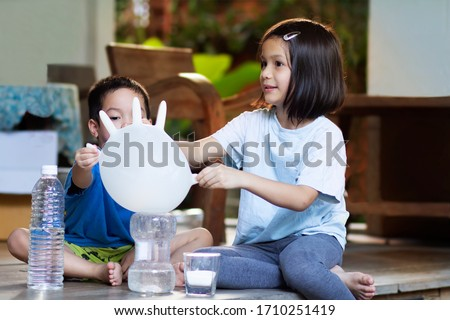 How baking Soda and Vinegar inflates rubble glove balloons  experiment. Asian preschool kids  learn to make an acid-base reaction. The reaction  carbon dioxide gas that bubbles up and glove bigger. #1710251419