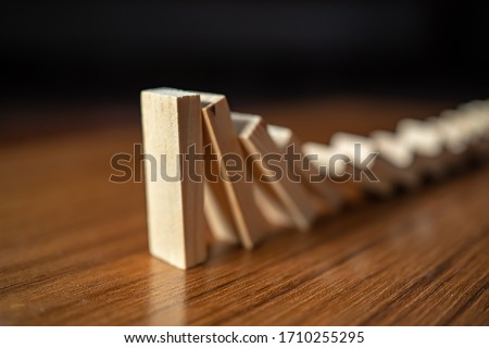 Falling dominoes on wooden table