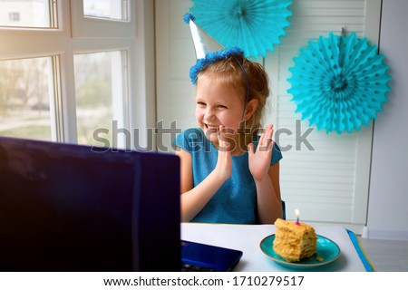 Little happy girl claps her hands, celebrates birthday via the internet in quarantine time, self-isolation and family values, online birthday Royalty-Free Stock Photo #1710279517