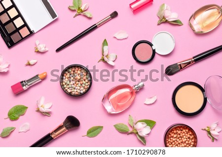 Decorative cosmetics mascara powder lipstick eyeshadow blush balls makeup brush perfume blooming spring branches on pink background top view Flat lay. Beauty blogger concept. Fashion background Royalty-Free Stock Photo #1710290878
