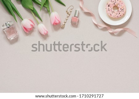 Spring concept banner for a blog. Pink tulips, nail Polish, eau de toilette and a bracelet on a dusty beige background with copy space. Fashion blogging #1710291727