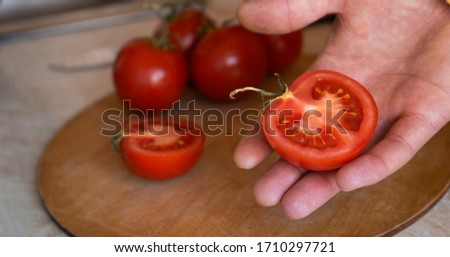 Cut the tomato into two pieces of red color lying in the hand. Fresh tomatoes for use as cooking ingredients with a tomato in the foreground with copy space #1710297721