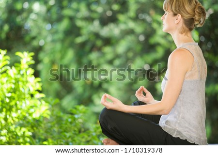 A young woman meditating outside #1710319378