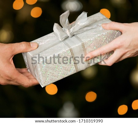 A gift wrapped present being exchanged #1710319390