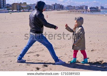 A young boy holding a kite in the snow. Little girl plays with dad at the beach. Joint games, relationships of children and parents. High quality photo