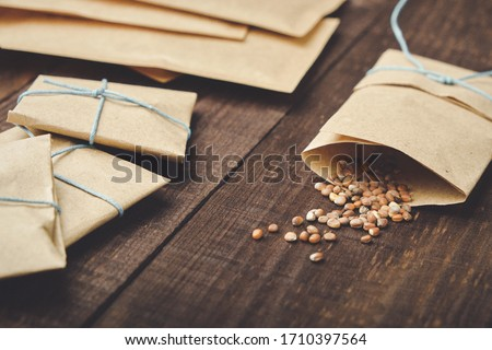 Paper bags with seeds for planting. Sprinkled radish seeds. Wooden table. Royalty-Free Stock Photo #1710397564