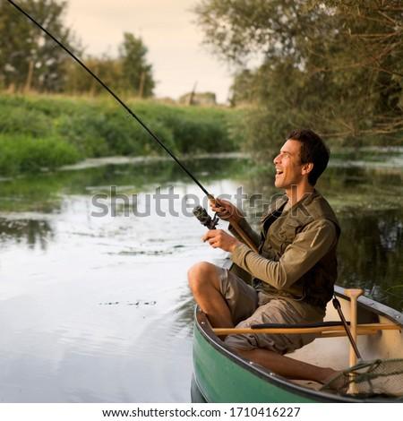 Young man fishing on a beautiful lake #1710416227