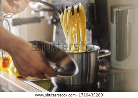 Man cooking pasta spaghetti at home in the kitchen. Home cooking or italian cooking concept.  #1710435280