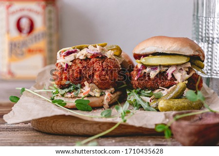 Spicy southern style fried chicken sandwich with coleslaw and pickles. Toasted burger buns. Fast food. Deep fried chicken.Rustic food photo.Crispy chicken breast.Breaded fried chicken. Unhealthy food. #1710435628