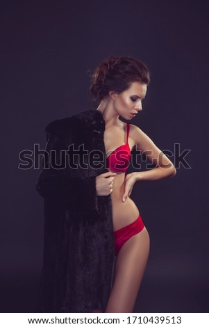 Beautiful sexy long-haired brunette woman in black lingerie and fur coat posing in the studio. The beauty of the face and body. Photos shot in a studio. #1710439513