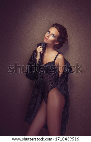 Beautiful sexy long-haired brunette woman in black lingerie and fur coat posing in the studio. The beauty of the face and body. Photos shot in a studio. #1710439516